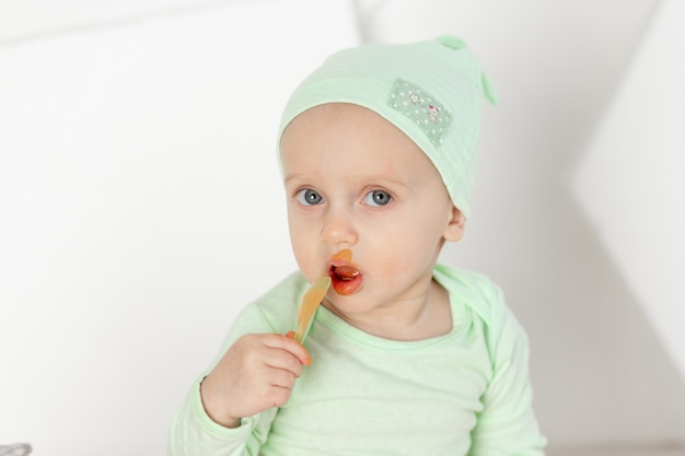 Bebê comendo colher de purê de frutas em traje verde, retrato, alimentação e conceito de comida para bebê
