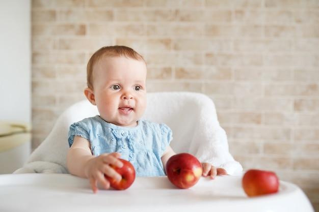 Bebê comendo frutas. menininha, morder, maçã amarela, sentando, em, branca, cadeira alta, em, ensolarado, cozinha