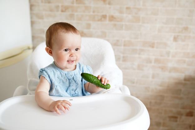 Bebê comendo legumes. pepino verde na mão da menina na cozinha ensolarada.