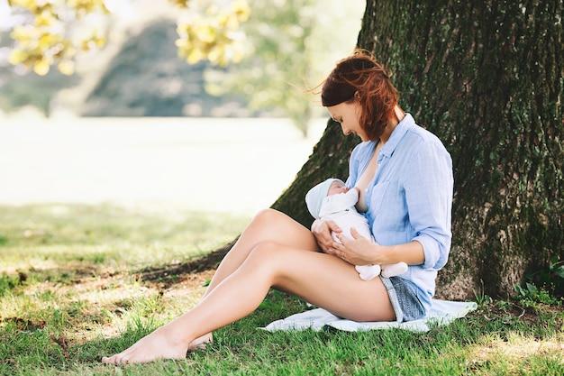 Bebê comendo leite materno na natureza. mãe amamentando bebê