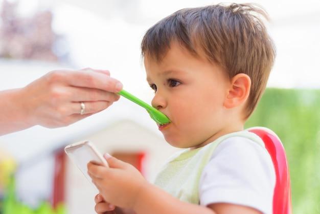 Bebê comendo o almoço enquanto olha para o smartphone