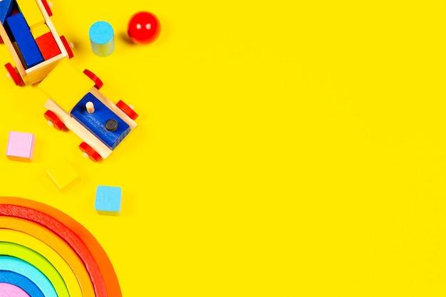 Bebê criança brinquedos fundo de madeira brinquedo trem arco-íris de madeira e blocos coloridos em fundo amarelo vista superior plana lay