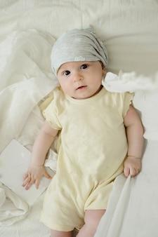 Bebê curioso de quatro meses com um cartão vazio em um vestido amarelo
