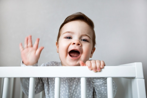 Bebê curioso gritando e de pé em uma cama branca do berço.