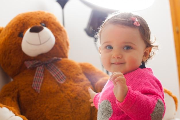 Bebé da criança que joga com o urso de peluche grande
