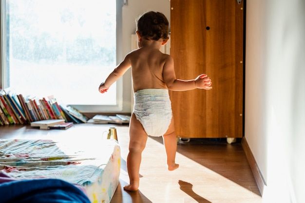 Bebê dando os primeiros passos com os pés descalços