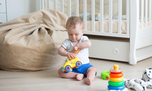 Bebê de 10 meses brincando no chão com carrinho de brinquedo e blocos