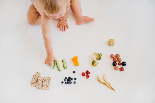 Bebê de alto ângulo escolhendo o que comer sozinho