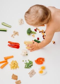 Bebê de alto ângulo escolhendo o que comer