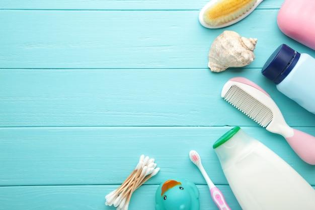 Bebê de artigos de higiene pessoal sobre fundo azul de madeira.