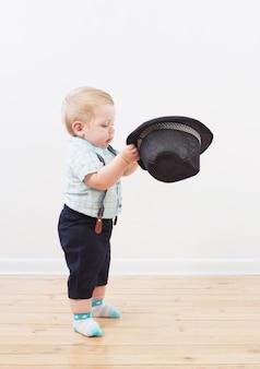 Bebê de boné preto, camiseta e shorts suspensórios em casa