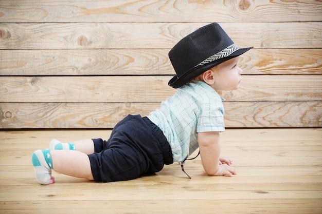 Bebê de chapéu preto, camiseta e shorts suspensórios em superfície de madeira