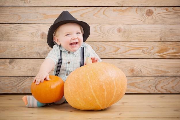 Bebê de chapéu preto com abóboras em fundo de madeira