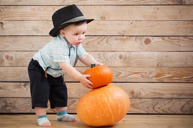 Bebê de chapéu preto com abóboras na madeira