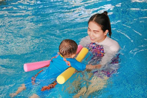 Bebê de ensino da mãe asiática do close-up na piscina com espuma do macarronete.