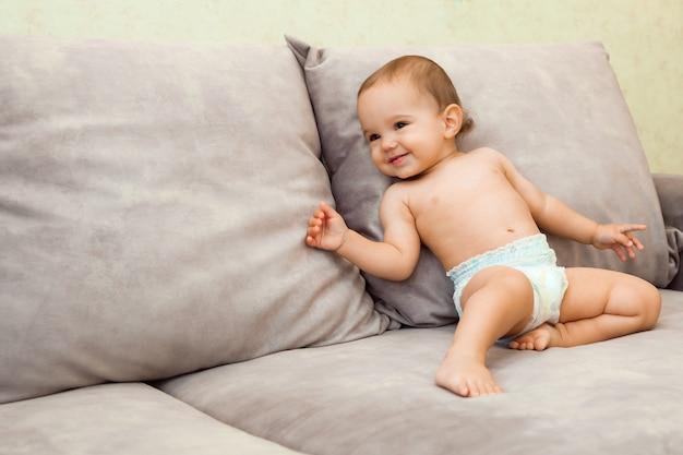 Bebê de fralda engatinha no sofá. bebê tem 11 meses.