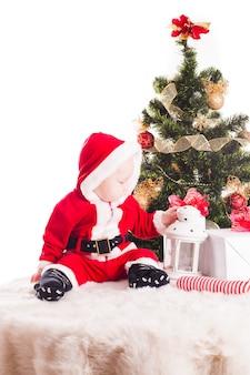 Bebê de natal embaixo da árvore de ano novo com presentes