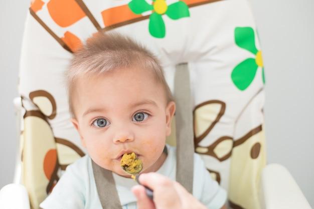 Bebé de olhos azuis que come na cadeira do bebê