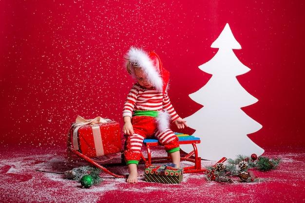 Bebê de pijama de natal e chapéu de papai noel pega neve sentado em um trenó com caixa de presente e grande árvore de natal branca em fundo vermelho