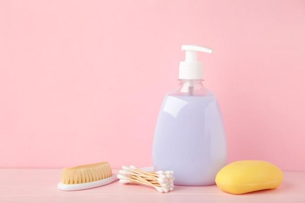 Bebê de produtos de higiene pessoal na parede rosa. gel de banho de bebê. vista do topo