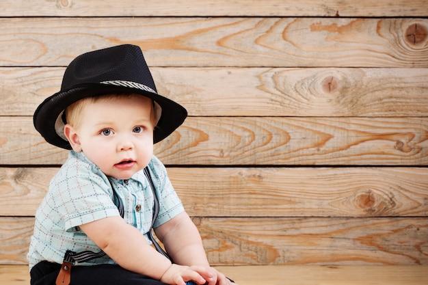Bebê de short preto de chapéu, camisa e suspensórios em fundo de madeira