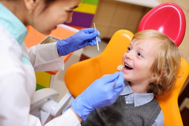 Bebé de sorriso com cabelo curly louro na cadeira dental.