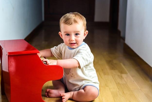 Bebê de sorriso que joga um piano do brinquedo ao aprender a música.