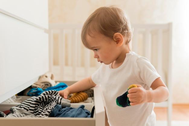 Bebê de tiro médio procurando na gaveta