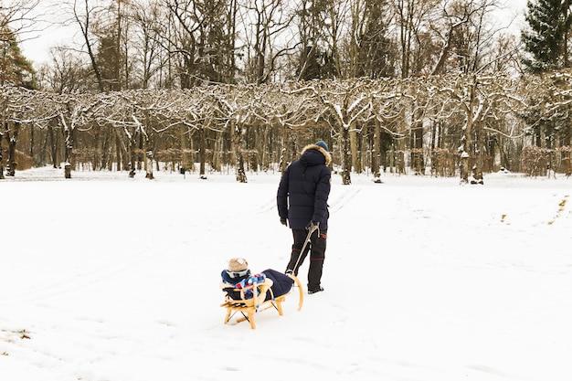 Bebê de trenó na neve na floresta