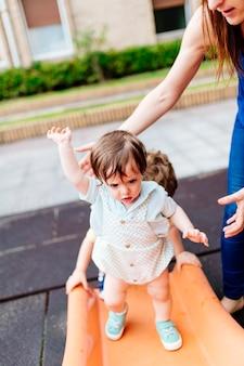 Bebê de três anos se equilibrando em um escorregador de um parque. risco de queda
