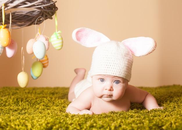 Bebê de três meses deitado de bruços como um coelhinho da páscoa na grama com ovos
