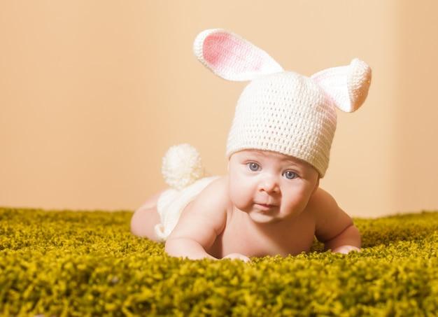 Bebê de três meses deitado de bruços como um coelhinho da páscoa no tapete de grama