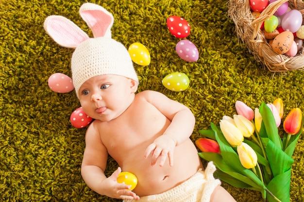 Bebê de três meses deitado no tapete de grama como um coelhinho da páscoa