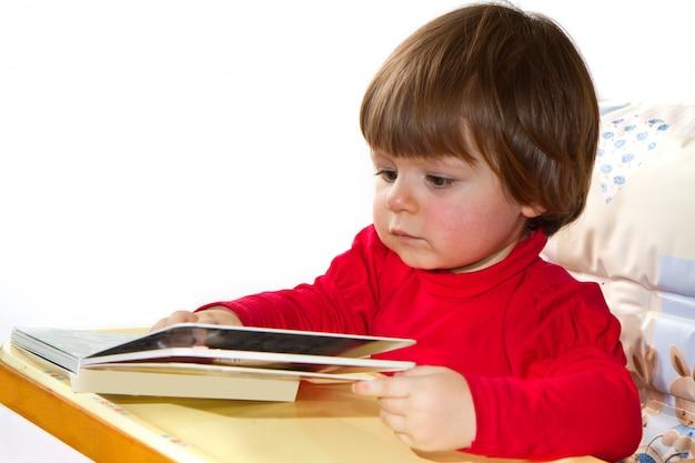 Bebê de um ano de idade adorável lendo um livro