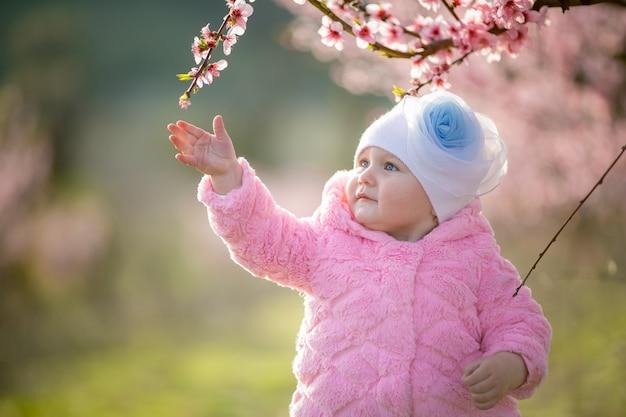 Bebê de um ano em um retrato de close-up de jaqueta rosa em um jardim de pêssego florescendo