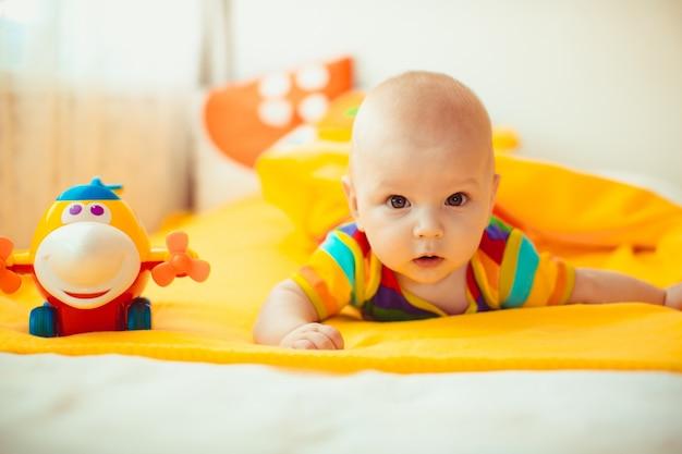 Bebê deitado em uma cama amarela