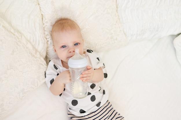 Bebê deitado na cama de pijama e bebendo leite em uma mamadeira