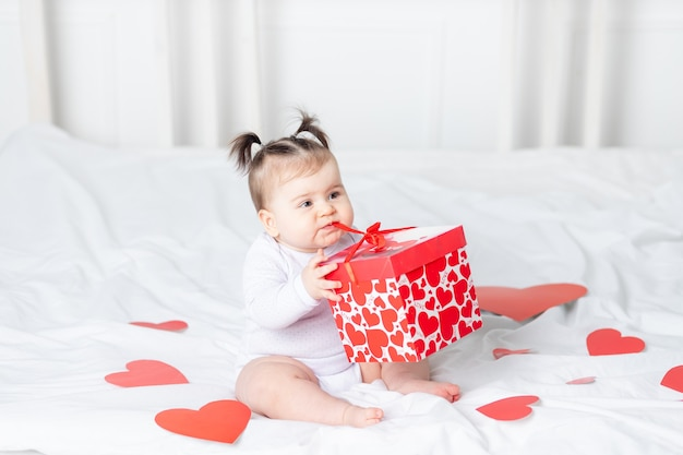 Bebê desata a caixa na cama em casa entre corações, conceito do dia dos namorados
