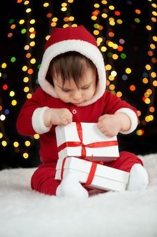 Bebê desempacota caixas de presente vestido como luzes de papai noel em fundo escuro