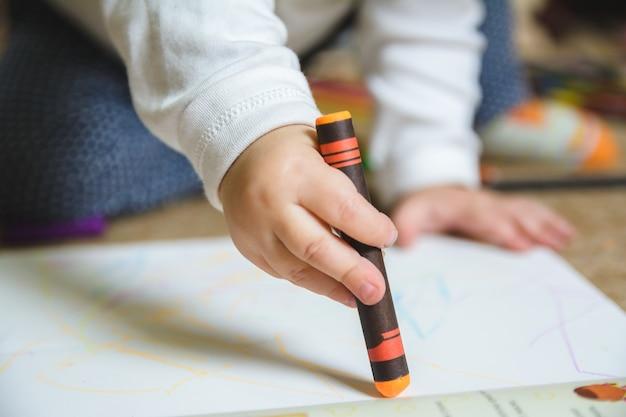 Bebê desenhando com giz de cera laranja no papel