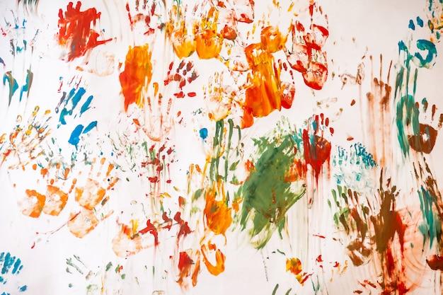 Bebê desenho com aquarela sobre fundo de parede branca. trabalhos de desenho abstrato de criança. impressões de mãos de crianças coloridas e manchas de sujeira nas fotos. fundos únicos para criatividade e papel de parede