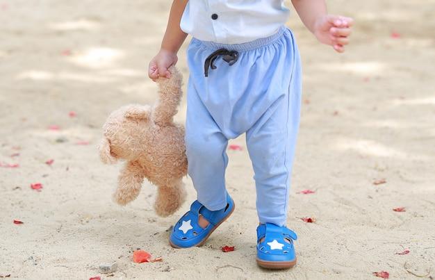 Bebé do close-up que anda com o urso de peluche da terra arrendada no jardim ao ar livre.