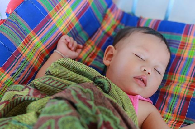 Bebé do close-up que dorme na cama com o cobertor.