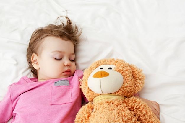 Bebê dorme com um urso de brinquedo