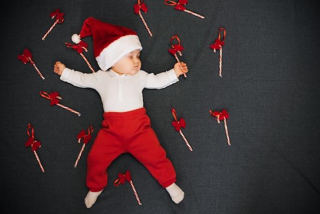 Bebê dormindo com doces de natal na mão e pirulito