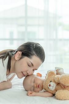 Bebê dormindo com um ursinho de pelúcia e mãe cuidando deles