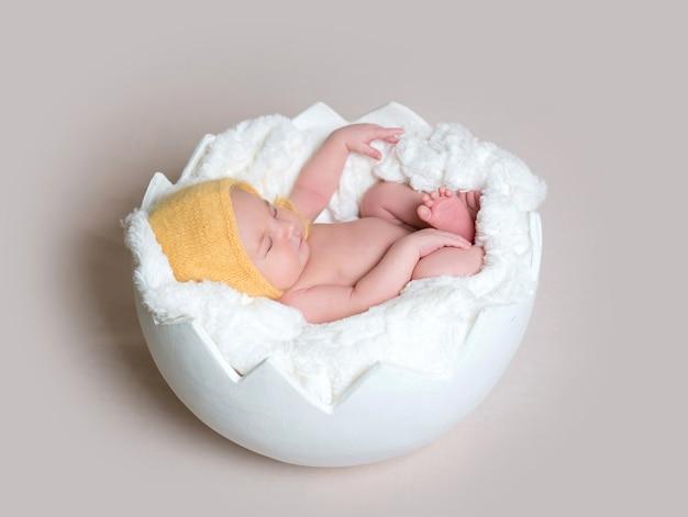 Bebê dormindo dormindo ovo casca usando gorro amarelo