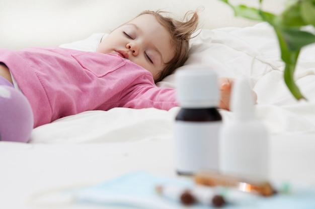 Bebê dormindo e medicação em desfocagem. conceito de tratamento de bebê