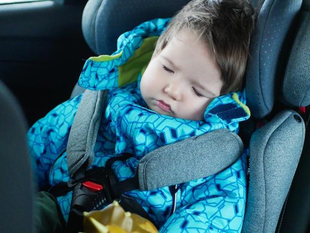 Bebê dormindo monta em um assento de carro. bebê feliz andar de carro. segurança para crianças. garoto bonito dormindo em um carro na cadeira de criança