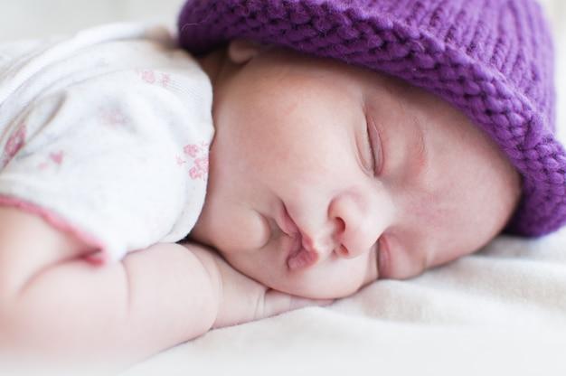 Bebê dormindo no chapéu roxo deitado no estômago